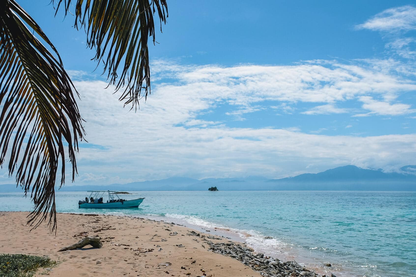 A beach in Cayos Cochinos with the mountains of Northern Honduras