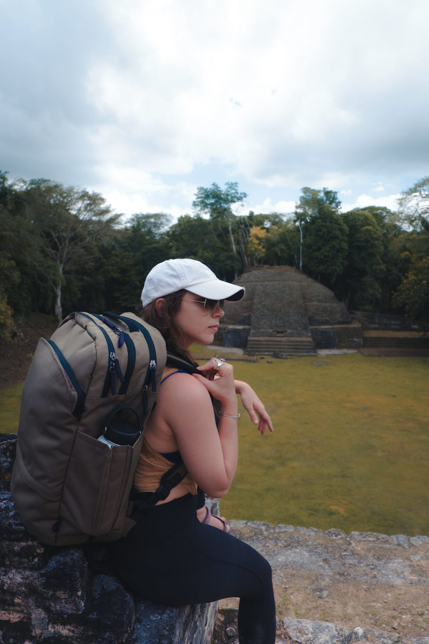 girl sitting on ruins at Caracol, Belize