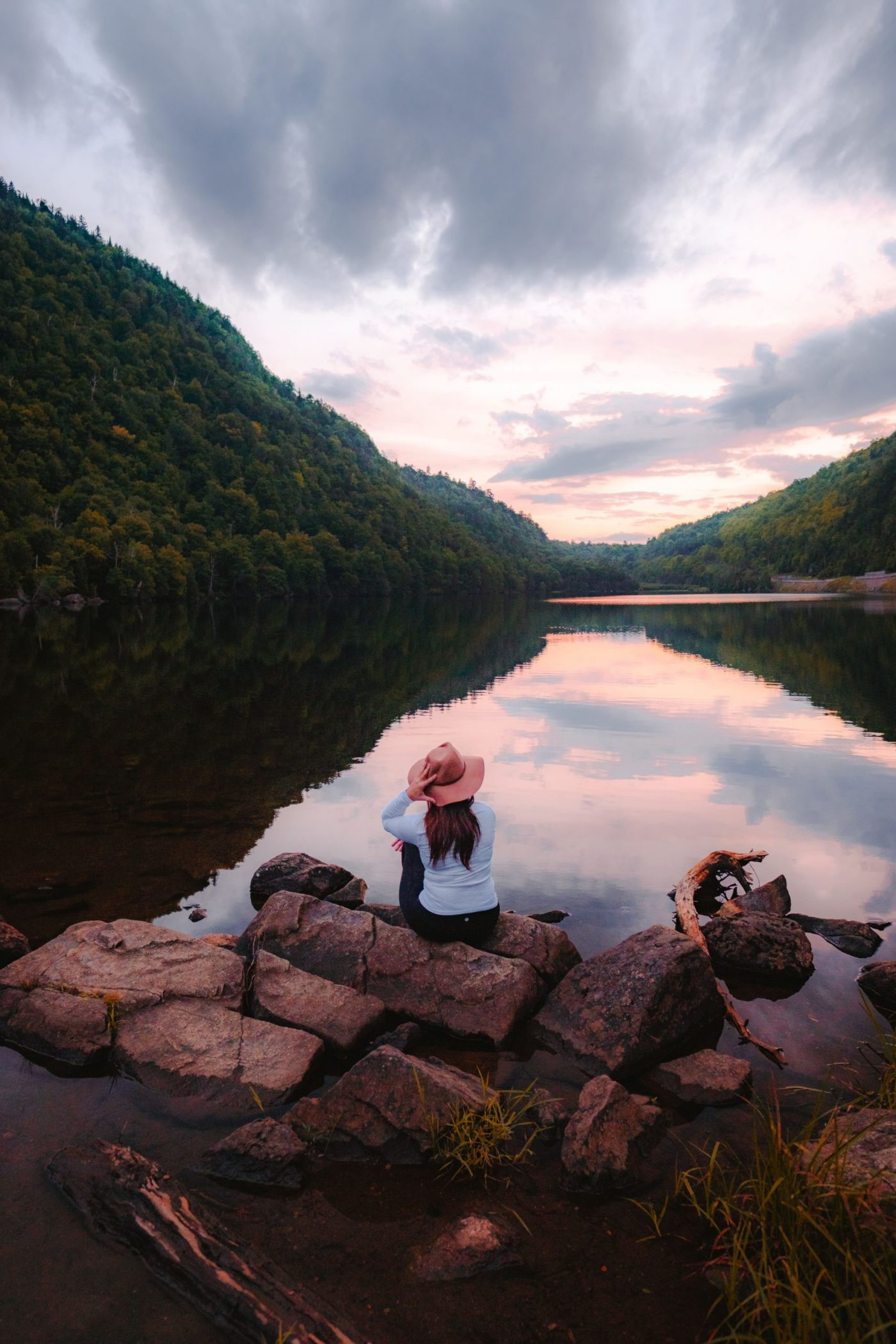 Girl sitting on the shore of a river in the Adirondacks during black fly season